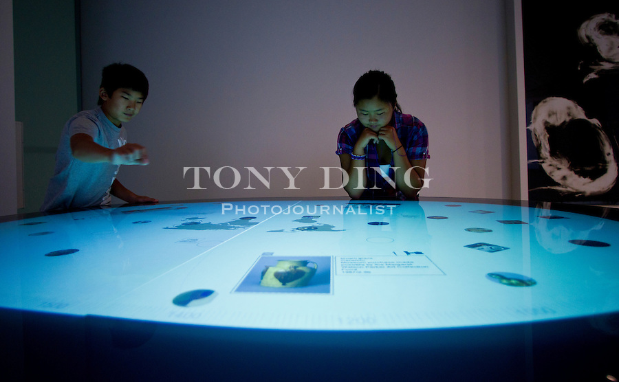 13-year-old Derek and sister Julia Trievwasser, 15, of Canton, Mich, play on an interactive display table in the University of Michigan's Museum of Art, Friday, Sept. 2, 2011 in Ann Arbor, Mich. (Tony Ding for The New York Times)