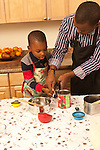 4 year old boy cooking with father learning how to open can with can opener