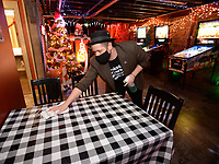 Bo Counts, owner of Pinpoint, wipes down tables with disinfectant Thursday, Jan. 7, 2021, as he and staff members prepare to open at the bar on Block Avenue in Fayetteville. The state's 11 p.m. curfew on serving alcohol has been extended to Feb. 3, and bar owners in Fayetteville filed a lawsuit to get the curfew lifted. Visit nwaonline.com/210108Daily/ for today's photo gallery. <br /> (NWA Democrat-Gazette/Andy Shupe)