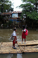 Schoolchildren stand on a river raft in a slum community in central Jakarta.<br />
