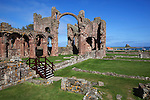 Great Britain, England, Northumberland, near Berwick-upon-Tweed: Ruins of Lindisfarne Priory with Lindisfarne Castle on Holy Island in distance