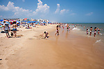 Adults and children alike enjoy the shallows on a hot summer day at Rehoboth Beach, Delaware, USA.