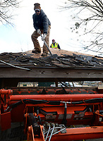 Nathan Albertson, a longtime worker with the city of Fayetteville Parks and Recreation Department, removes shingles Friday, Jan. 8, 2021, from the roof of a gazebo and loads them into the bucket of a backhoe in Walker Park. In addition to the gazebo's renovation, there are plans to make improvements to the park's bathroom buildings. Visit nwaonline.com/210109Daily/ for today's photo gallery. <br /> (NWA Democrat-Gazette/Andy Shupe)