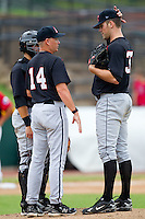 Kannapolis Intimidators pitching coach Larry Owens #14 has a chat with Matthew Hopps #37 as Kevin Dubler #35 listens in at  L.P. Frans Stadium August 1, 2010, in Hickory, North Carolina.  Photo by Brian Westerholt / Four Seam Images