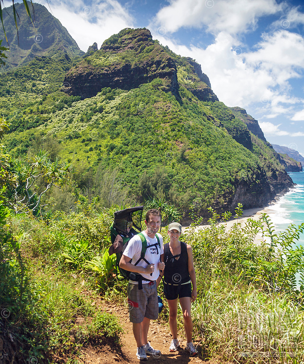 Two hikers with their baby daughter pause on the Kalalau Trail along the Na Pali Coast, Kaua'i.
