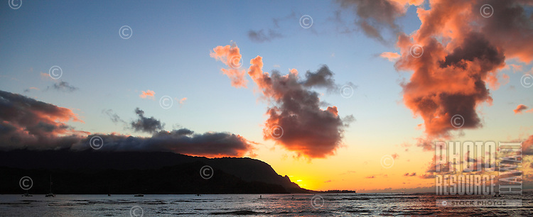 As the sun sets behind Mt. Makana (also called Bali Hai), a distant standup paddler and others makes the most of the light at Hanalei Bay, Kaua'i.