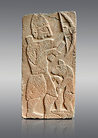 Pictures & images of the North Gate Hittite sculpture stele depicting Hittite man with abow and a bear. 8th century BC. Karatepe Aslantas Open-Air Museum (Karatepe-Aslantaş Açık Hava Müzesi), Osmaniye Province, Turkey. Against grey background