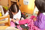 Education preschool 3-5 year olds girl helping friend buckling her shoe for her