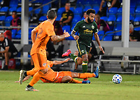 LAKE BUENA VISTA, FL - JULY 18: Eryk Williamson #30 of the Portland Timbers tries to dribble past a sliding opponent during a game between Houston Dynamo and Portland Timbers at ESPN Wide World of Sports on July 18, 2020 in Lake Buena Vista, Florida.