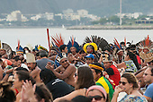 Indigenous people and others are assembling the human banner on Flamengo beach to protest about the construction of hydroelectric dams on Brazil's rivers with the Sugarloaf in the background. Kayapo Chief Raoni is in the centre of the picture wearing a yellow feather headdress. The People's Summit at the United Nations Conference on Sustainable Development (Rio+20), Rio de Janeiro, Brazil, 19th June 2012. Photo © Sue Cunningham.