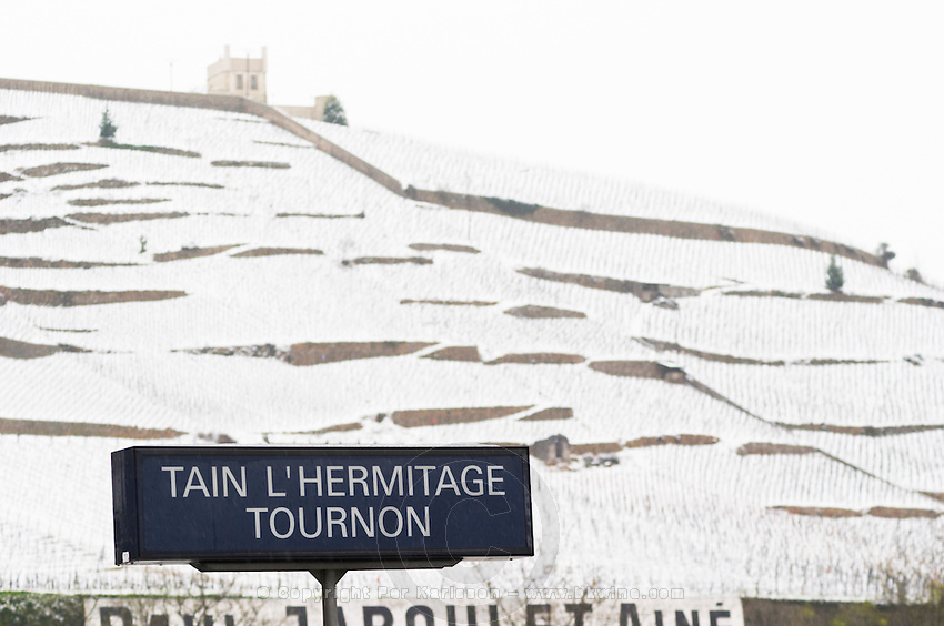 The Maison Blanche White House vineyard and the sign at the railway station for Tain l'Hermitage Tournon. Sign in focus. The Hermitage vineyards on the hill behind the city Tain-l'Hermitage, on the steep sloping hill, stone terraced. Sometimes spelled Ermitage. Vineyards under snow in seasonably exceptional weather in April 2005. Tain l'Hermitage, Drome, Drôme, France, Europe