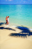 Senior Couple walking in the surf. romance, beach, ocean, seascape, couples, shadow of a palm tree. Brian Nurding, Theo Davis See. Oahu Hawaii.