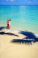 Senior Couple walking in the surf. romance, beach, ocean, seascape, couples, shadow of a palm tree. Brian Nurding, Theo Davis See. Oahu Hawaii.