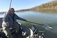 Mike McBride comes prepared with a net to land big crappie at Lake Sequoyah in Fayetteville. Small silver and black jigs rigged three feet under a float on March 4 2021 did the trick. McBride has been fishing at Lake Sequoyah since he was a boy. <br />(NWA Democrat-Gazette/Flip Putthoff)