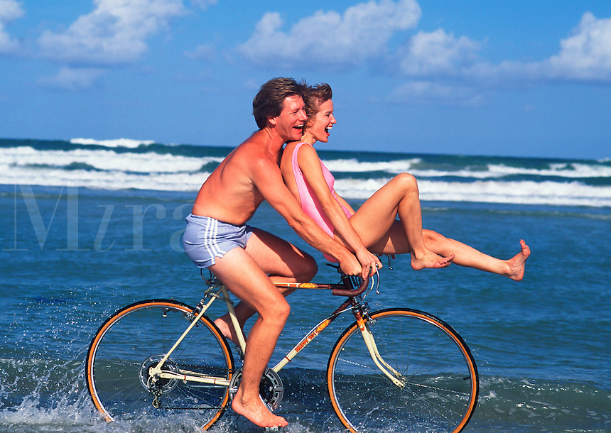 Middle-aged couple riding a single bike on beach