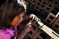 A 5-year-old Peruvian girl plays with bricks while helping her parents at a brick factory in the outskirts of Puno, Peru, 6 August 2012. Child labour is a common practice at the artisanal brick factories, found predominantly in socially deprived areas of the urban zones. Poverty and lack of employment force parents, mainly season workers coming from rural areas of the country, to employ their own children, in an effort to ensure the livelihood for the whole family. Children aged 4-7 take part in simple jobs while children aged 8 and up tend to work regularly, same as adults. A family group, consisting of 2 adults and 2-3 children, may earn 20-25 USD per day, working almost the whole day, often in harsh climatic conditions.