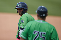 Orlando Arcia (13) of the Gwinnett Stripers smiles at first base coach Wigberto Nevarez (25) during the game against the Charlotte Knights at Truist Field on May 9, 2021 in Charlotte, North Carolina. (Brian Westerholt/Four Seam Images)