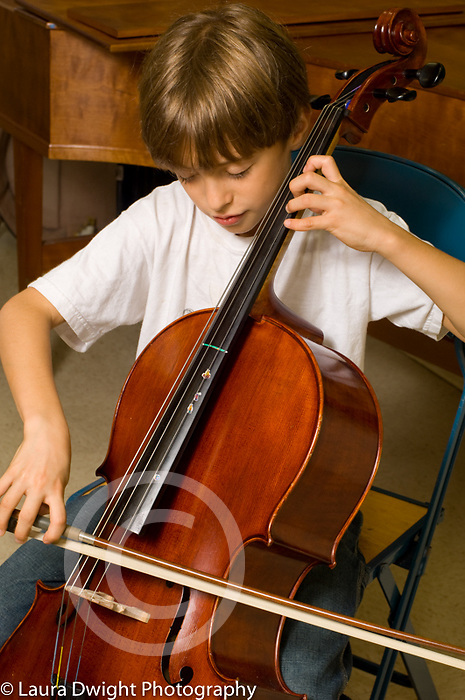 9 year old boy playing the cello at public school with enriched music program