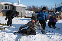 "Students from Zackar Levi School in Lower Kalskag don their skis as they prepare to descend ""Dog Hill."" Skiku is a non-profit organization with the mission of creating a sustainable Nordic ski program in communities throughout Alaska. Volunteer coaches travel to villages each spring to instruct youngsters and distribute donated equipment with the goal of establishing ski programs at rural schools.  Photo by James R. Evans"