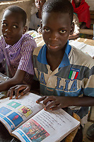 Senegal, Touba.  Young Boy at Al-Azhar Madrasa, a School for Islamic Studies.  His book shows that he is studying Arabic.