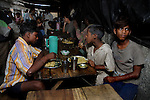 Alamgir and his friends during a sponsered lunch by Mukti Rehab a NGO who works with drug addicted children at the Sealdah railway station. He is staying at Sealdah station for last 6 years from the time he ran away from his home due to domestic violence and poverty. As per his version his father was a drunkard and used to beat his mother for no reason. His father even could not earn enough money to buy food for their big family. Due to this traumatic situation he ran away from house at the age of seven. Ever since, the Sealdah railway station in Kolkata has been his home. As far as company is concerned, he had not much reason to miss his family. There are around 500 children, from 5 to 16 years, who live in the premises of Kolkata's second largest train terminus. Most of them addicted to Brown Sugar and sniffing industrial adhesive Dendrite. They say they don't feel hungry if they take the drugs. Their presence is conspicuous, even in a place that registers an average footfall of 1.4 million on weekdays. Their activities cover a wide range, from begging, to pulling handcarts, to petty theft, to selling odds and ends on the platform or on trains. The money, earned or ill-gotten as the case may be, is spent in procuring heroin, brown sugar, cocaine, and tubes of Dendrite. Calcutta, West Bengal, India. Arindam Mukherjee
