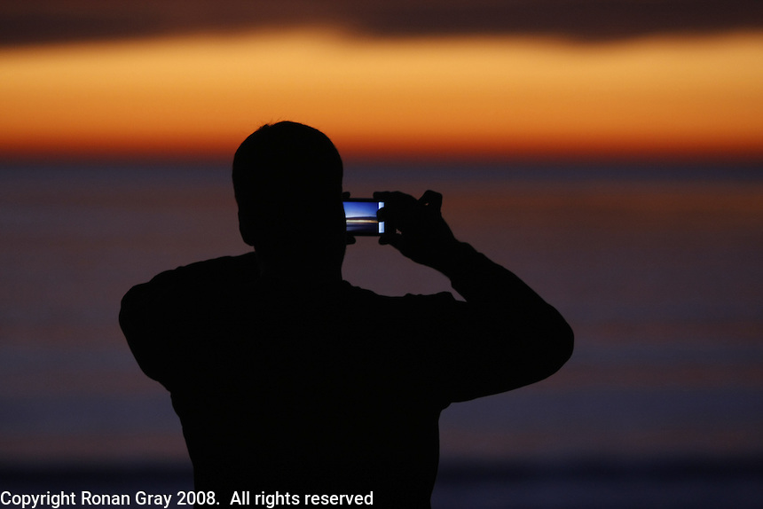 Pacific Beach, San Diego, California, USA:  Monday, January 19 2009.  John Hewick of La Jolla photographs the sunset from the park above the beach at the foot of Law Street.  The Martin Luther King Jnr Day holiday in San Diego was marked by warm weather, big surf and a technicolored sunset as much of the rest of the country shivered in the cold.  The sunset was the last one for the Bush Administration as the country prepares for the inauguration of Barack Obama tommorow.
