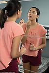 17 year old teenage girl looking at self in mirror, applying makeup