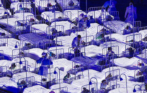 "27 JUL 2012 - LONDON, GBR - A doctor and nurse walk between the beds of sleeping children during the ""Second To The Right, And Straight On Till Morning"" section of the Opening Ceremony of the London 2012 Olympic Games in the Olympic Stadium in the Olympic Park, Stratford, London, Great Britain .(PHOTO (C) 2012 NIGEL FARROW)"