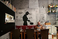 A diner awaits his meal at the restaurant 'Chat Noir, Chat Blanc', Nice, France, 10 April 2012. Artwork on the walls was inspired by pages taken from sous-chef Nicolas Sikic's grandmother's personal recipe book. Her handwritten recipies were enlarged and montaged with silhouettes modelled on the two chefs, Giorgio Grilenzoni and Nicolas (artwork by Nomada).