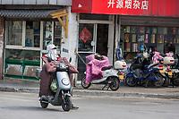 Suzhou, Jiangsu, China.  Woman with Breathing mask Riding Electric Motorbike.