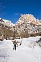 Walker on snow shoes leaves the hamlet of Archiane in the Cirque d?Archiane in deep snow.  Diois, Drome, Rhone-Alpes, France.