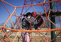 Sagan Gregory of Rogers (from left) helps Silas Hackett, 3, climb down a jungle gym, February 22, 2021 at Osage Park in Bentonville. Check out nwaonline.com/210223Daily/ for today's photo gallery. <br /> (NWA Democrat-Gazette/Charlie Kaijo)