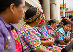 A group of Guatemalan woman in traditional dress sit and talk in Zunil, Guatemala in the Western Highlands