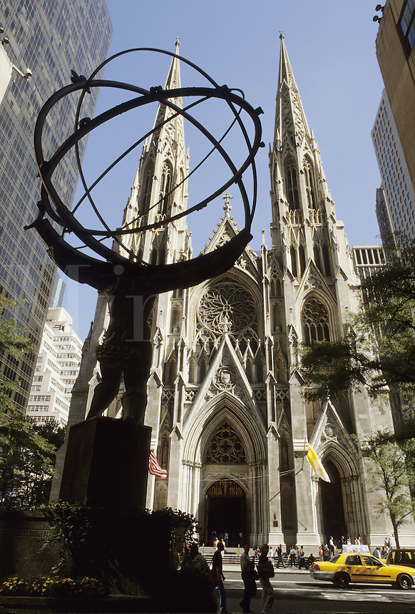 New York City,.   St. Patrick's Cathedral on 5th Avenue at 50th Street. The Atlas sculpture (fgd. silhouette) is in Rockefeller Center.