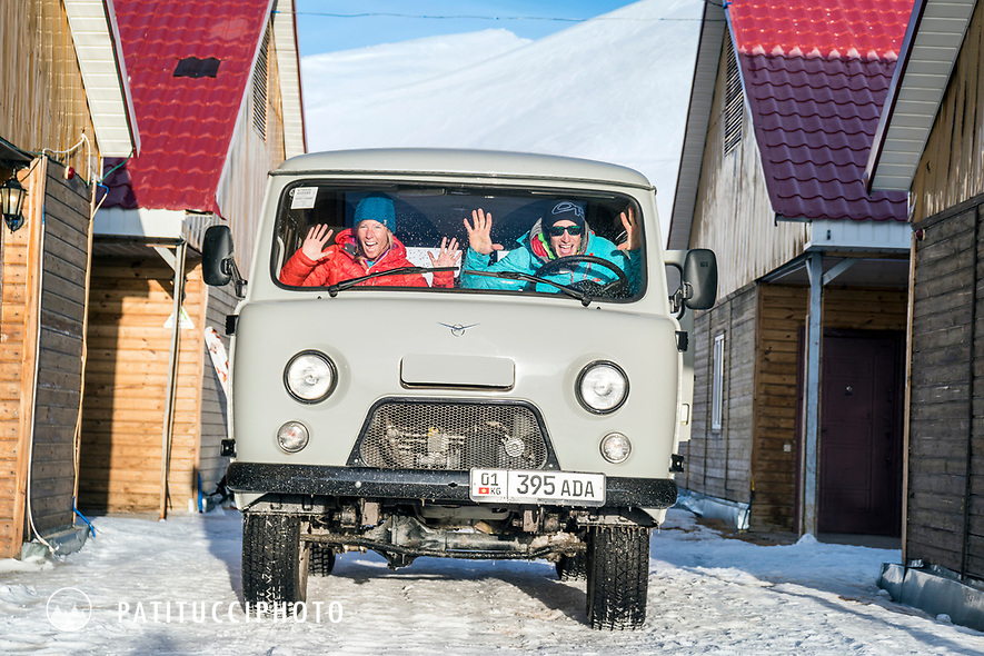 Two skiers traveling in Kyrgyzstan laugh while in their UAZ 452, a Russian made bus