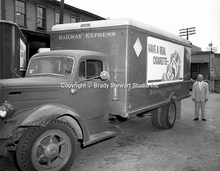Pittsburgh PA:  View of Railway Express Marketing Manager standing next to a truck with advertising on it.  The new advertising approach was a direct result of the company's financial problems during the 1950s.  Railway Express was a group of private transportation companies throughout the Pittsburgh area. Due to continued financial problems, Railway Express was taken over by the state in 1964 and the emerging company was called the Port Authority of Allegheny County.