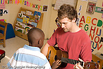 Preschool ages 3-5 visting teacher musician allowing boy to come up to strum the strings of his guitar horizontal