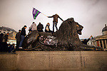 """© Joel Goodman - 07973 332324 . 26/03/2011 . London , UK . Protesters stand on a lion with """" Tory Scum """" spray painted on its side , in Trafalgar Square . Hundreds of thousands of people attend an anti cuts demonstration under the banner """" March for the Alternative """" in central London , in protest at the coalition government's austerity measures . Photo credit : Joel Goodman"""