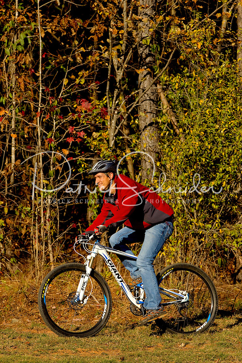 A man (model) enjoys mountain biking on a wooded trail at the US National Whitewater Center in Charlotte, NC. The USNWC, an ultimate adventure playground for outdoor enthusiasts, offers both water and land sports.