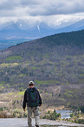 A hiker on the rocky summit of Middle Sugarloaf Mountain in Bethlehem, New Hampshire on a cloudy spring day. The Presidential Range can be seen in the background.