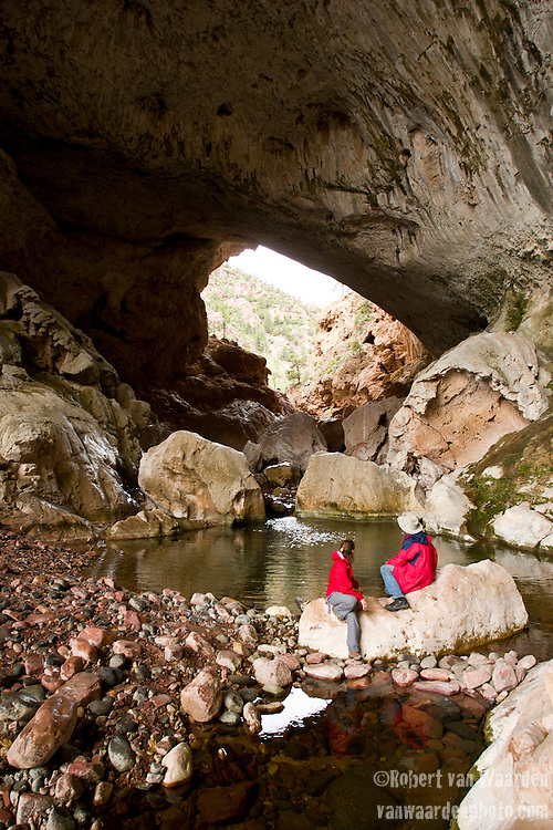 A man and a woman in red admire the geological formation of Tonto Bridge, Central Arizona, United States of America.