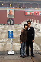 CHINA. Beijing.  A couple stand in front of the famous Mao Zedong portrait that hangs on the 'Gate of Heavenly Peace' which leads into the Forbidden City and is opposite Tiananmen Square. Mao is still revered in China even 30 years after his death and 40 years since the end of the 'Cultural Revolution' and the 'Great Leap Forward' where it is alleged he was responsible for the death of some 20 million Chinese people. Nevertheless, every day thousands of Chinese people make the pilgrimage to stand and have their photo taken in front of his most famous portrait. 2005.