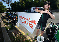 Garrett Adams, operations manager for Scoot Tribe, sets out a sign Tuesday, Sept. 7, 2021, welcoming back University of Arkansas students as he prepares for the day at the scooter and motorsports store in Fayetteville. The store offers scooters, motorcycles and ATVs for sale and provides service. Visit nwaonline.com/210908Daily/ for today's photo gallery.<br /> (NWA Democrat-Gazette/Andy Shupe)