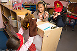 Education preschool childcare 4 year olds pretend play game one girl wearing puppets on hands interacting with two girls in dressup
