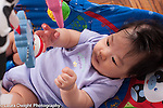 3 month old baby girl Asian Chinese American in baby seat with toy bar looking at dangling toys reaching to touch one horizontal