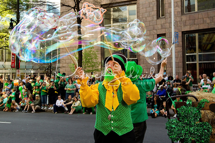 Photography of the Charlotte NC St. Patrick's Day Parade in March 2012. Image shows performers blowing giant bubbles as part of the parade. Photography is part of a series of St. Patrick's Day Parade photos in Charlotte, NC.