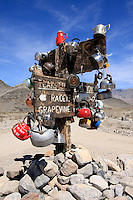 Teakettle Junction along Racetrack Valley Road in Death Valley National Park. Passersby hang teakettles, often inscribed with a message, on the signpost at the junction of Racetrack Valley Road and Hidden Valley Road in violation of National Park Service Policy. The tradition reportadly dates back to an early explorer of the area that left he teakettle at this junction and others have added their own. Photographed 4/08
