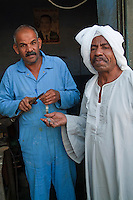 Man repairs the watchband of his client waiting alongside, Quoseir Village, Red Sea, Egypt.