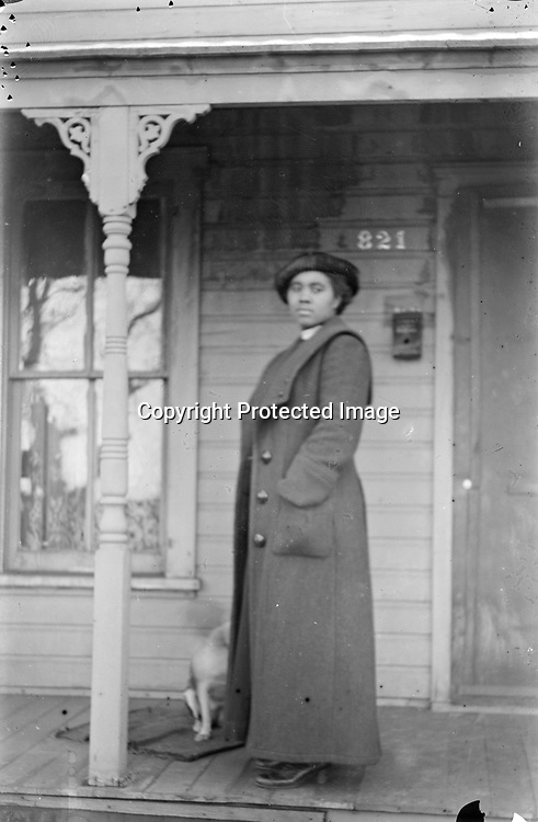 LADY AT NO. 821. This porch is probably 821 S Street, where Abraham and Ellen Corneal lived across the street from Lincoln's Missouri Pacific Railroad depot. Abraham was assistant baggage master. Whether the young woman is a Corneal, or Lena Carriger who lived at the address in 1923, is not known.<br /> <br /> Photographs taken on black and white glass negatives by African American photographer(s) John Johnson and Earl McWilliams from 1910 to 1925 in Lincoln, Nebraska. Douglas Keister has 280 5x7 glass negatives taken by these photographers. Larger scans available on request.