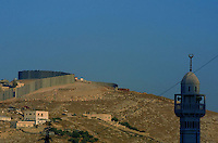A general view of Israel's controversial 8-meter-high (26 feet) security barrier that is still under construction June 30, 2004, in the Palestinian neighbourhood of A - Tur  in East Jerusalem. The Israeli High Court of Justice June 30, 2004 ordered changes to 30 kilometres of the route of the West Bank separation fence, northwest of Jerusalem, saying that everything must be done to minimize hardship to Palestinians living in the area. Photo by Quique Kierszenbaum
